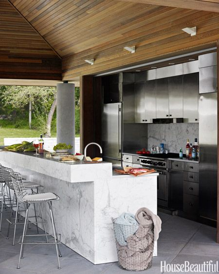 In designer Bonnie Edelman's Ridgewood, Connecticut house, the pool kitchen's stained white-oak ceiling pours warmth over cool metal custom stainless-steel cabinets.