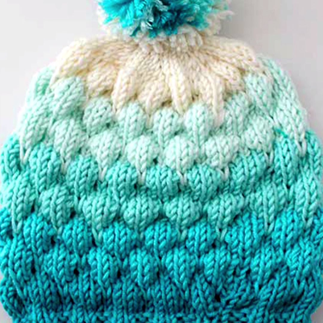 So fun to knit! This Bubble Beanie Hat knitting pattern is my new favorite fashion accessory! This knitted hat pattern is perfect if you enjoy changing yarn colors and are comfortable knitting on circular needles. This is also a great yarn stash buster. #StudioKnit #knittingvideo