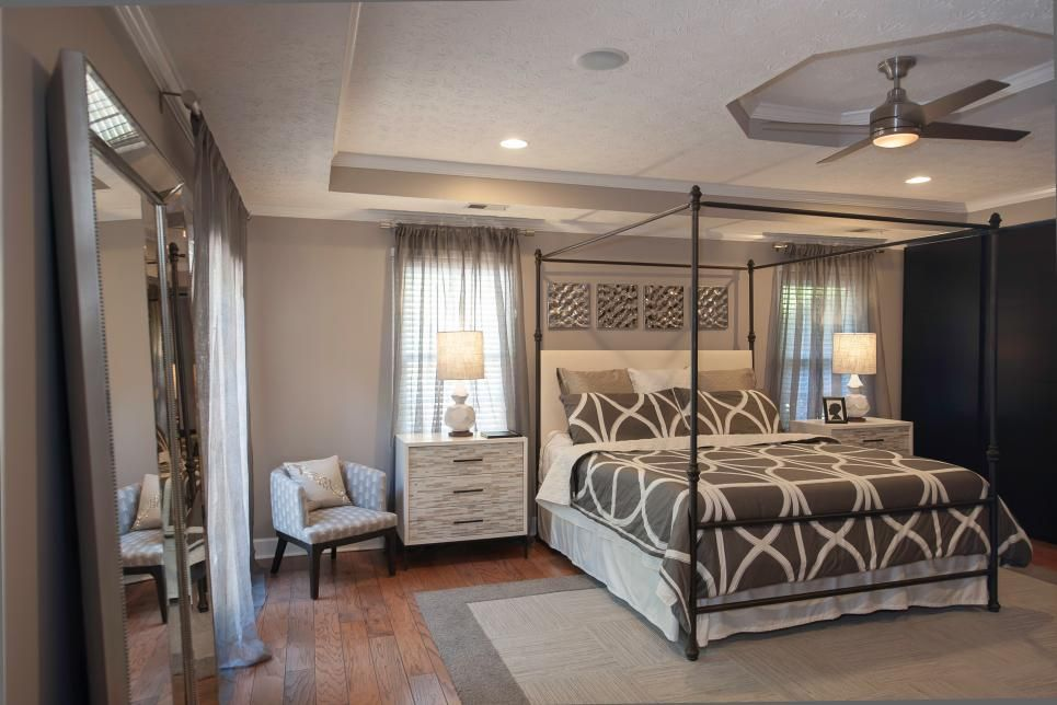 This chic master bedroom features an all-over gray palette, including soft gray walls and sheer curtains. White nightstands with heather gray drawers flank either side of the wrought iron canopy bed which boasts a gray and white patterned duvet cover. A two-toned gray area rug covers the floor.