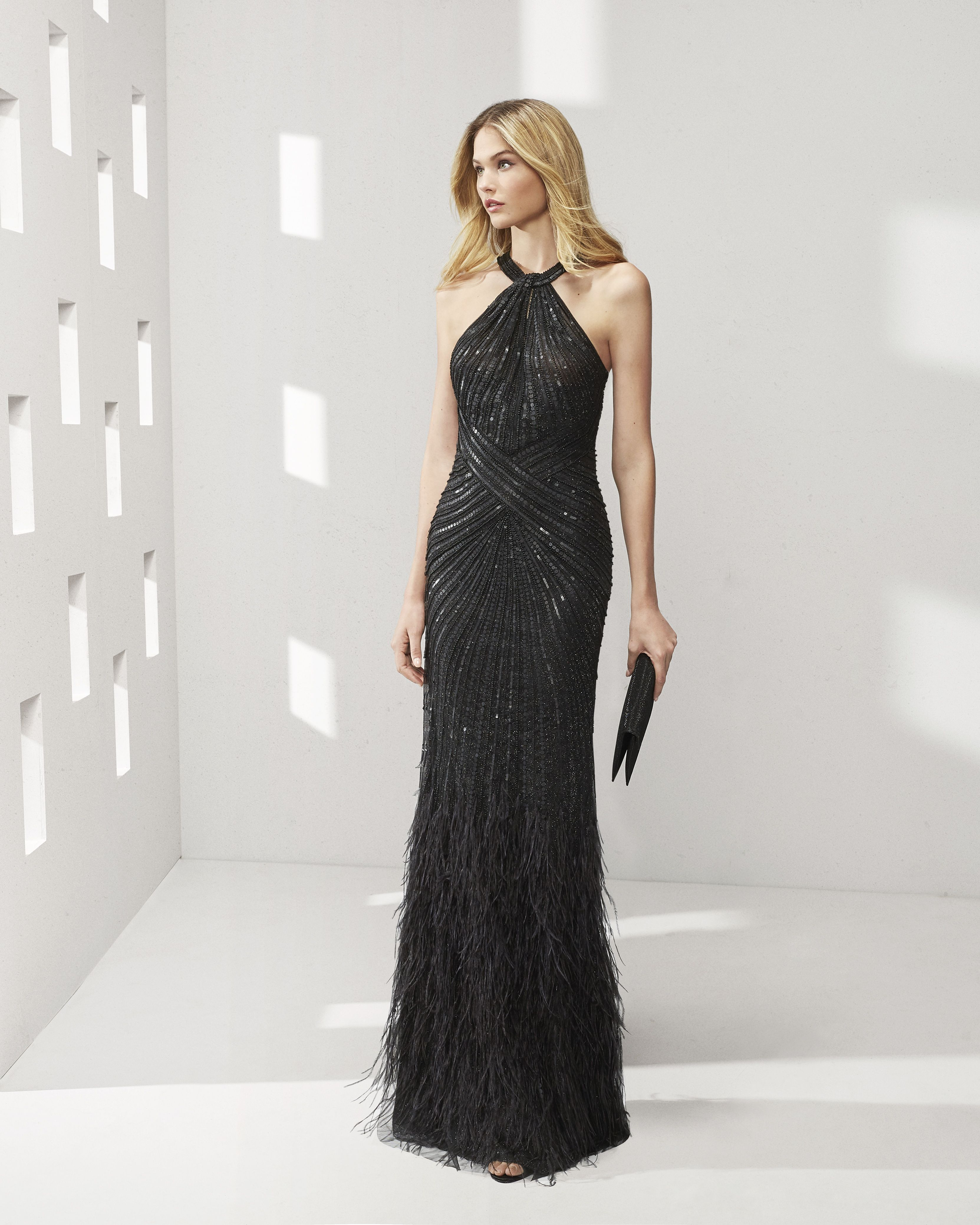 65770bda31 Long beaded cocktail dress with feathers at the hem. Halter neckline and  crossover back with