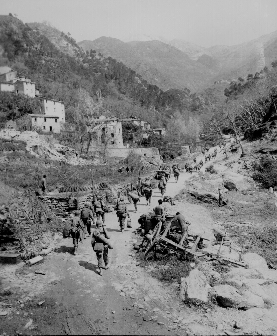 """""""Moving up through Prato, Italy, men of the 370th Infantry Regiment, have yet to climb the mountain which lies ahead."""" Bull, April 9, 1945."""