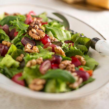Huuhtele ja valuta salaatit. Paahda pähkinät kuivalla pannulla, kunnes ne ovat saaneet hieman väriä., Revi salaatit tarjoiluastialle. Pilko paprika ja kurkku kuutioiksi tai suikaleiksi. Halkaise viinirypäleet., Ripottele paprika- ja kurkkipalat sekä viinirypäleet salaatin päälle. Koristele saksapähkinöillä ja basilikalla. Lorauta päälle oliiviöljyä.