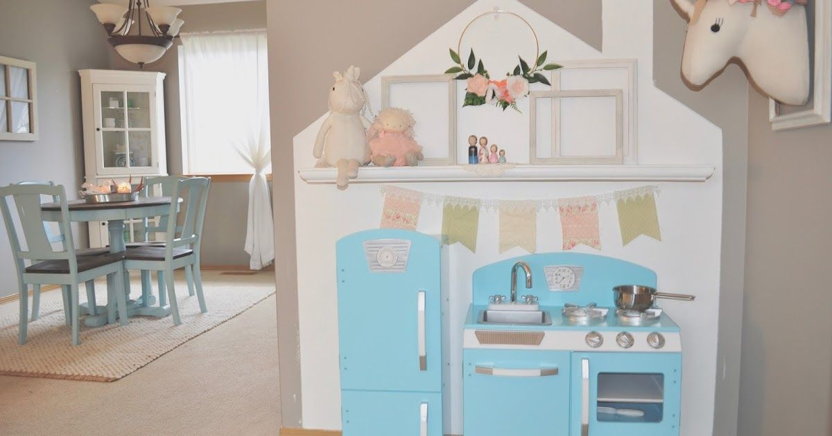 Blue play area kitchen with house stencil painted on the wall. Felt flowers, unicorn, and empty frames for decoration.