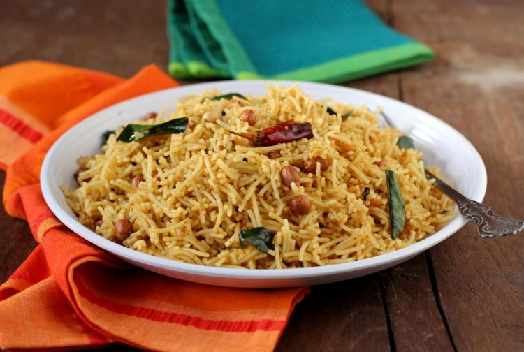 Puli Sevai is tamarind flavored Idiyappam. Rice string hoppers tossed in a tempered spices,  flavored with tamarind and garnished with roasted peanuts. Makes for a filling vegan meal.