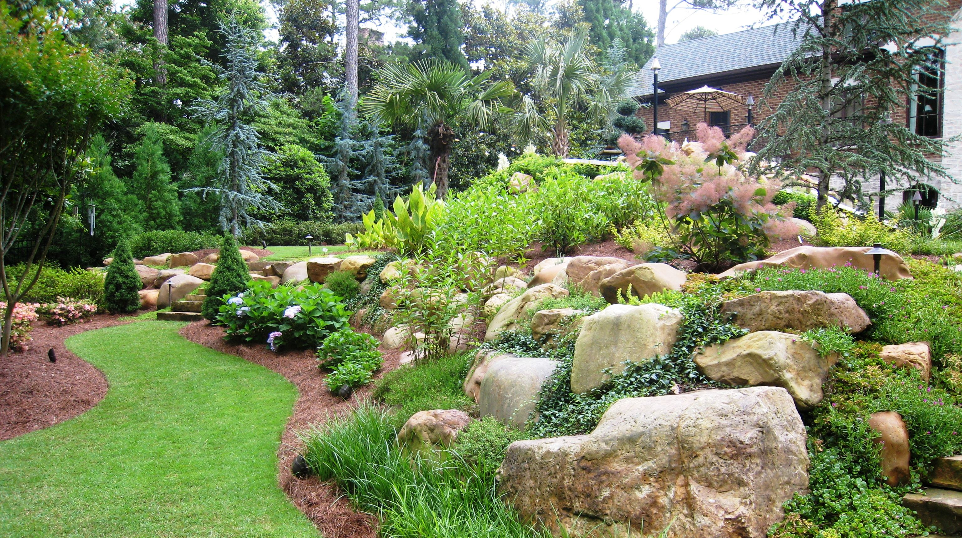 Large natural boulders combined with shrubs and perennials for Large bushes for landscaping