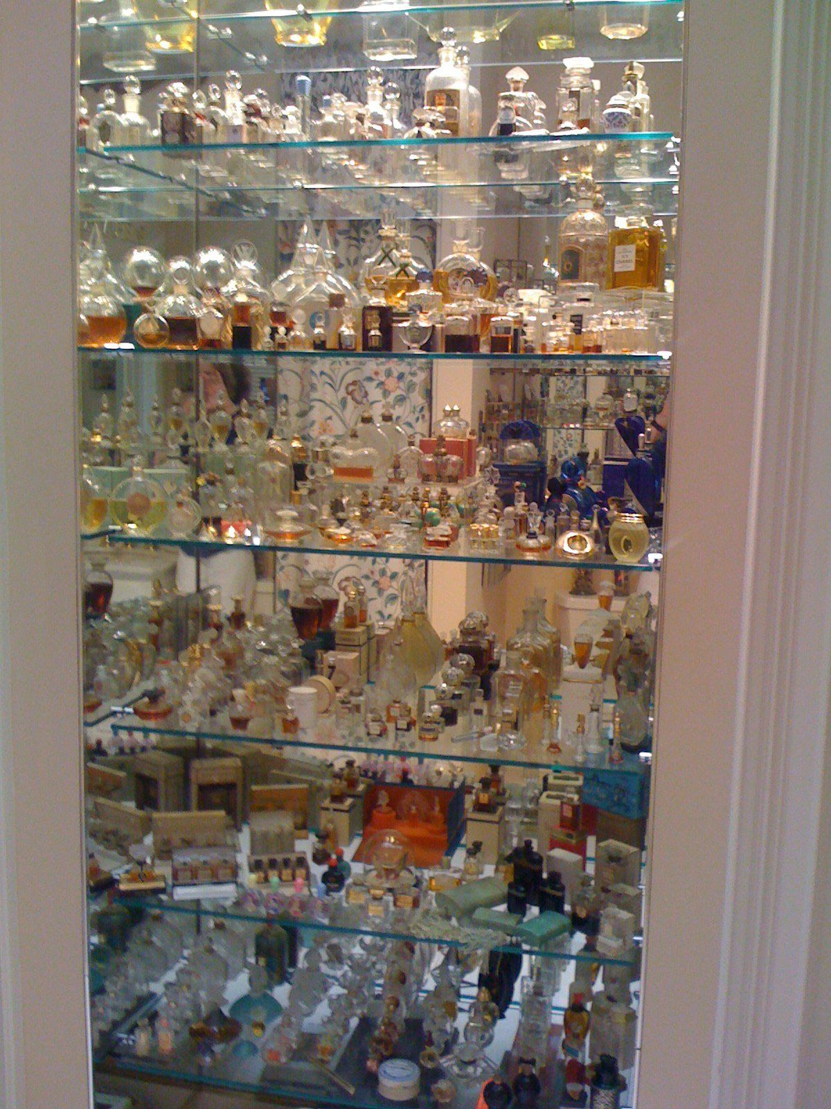 Perfume Bottles On Shallow Glass Shelves With Mirror