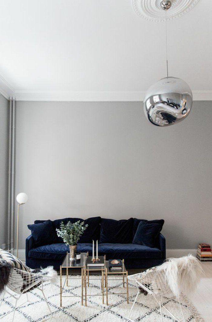 tapis blanc noir canape bleu fonce table en verre et metal lustre boule mur gris