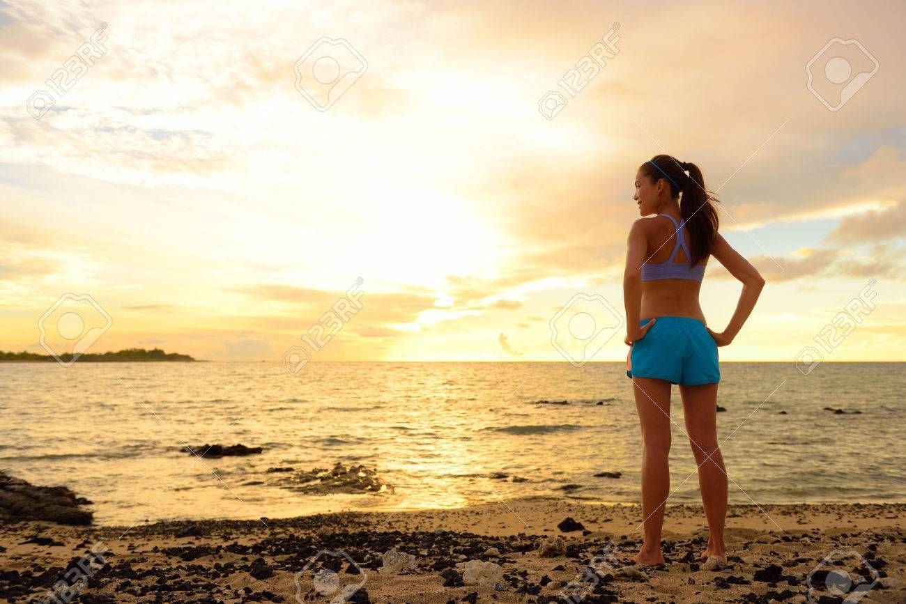 Aspirations - woman looking away with inspiration. Fitness woman after run in sunset on beach lookin...