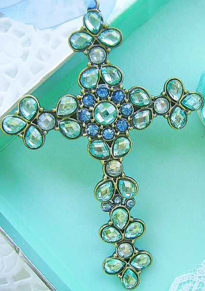 """Beautiful Bejeweled Light Aqua Cross    This beautiful metal cross is bejeweled with stunning light aqua blue and white faceted bling! stunning sparkle when the light catches it! Measures 4.25"""" x 3"""". Hangs from sheer organza ribbon.  Price:$10.99"""