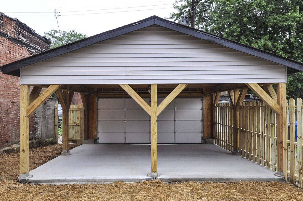 Another view of garage carport garage door and privacy fence on the