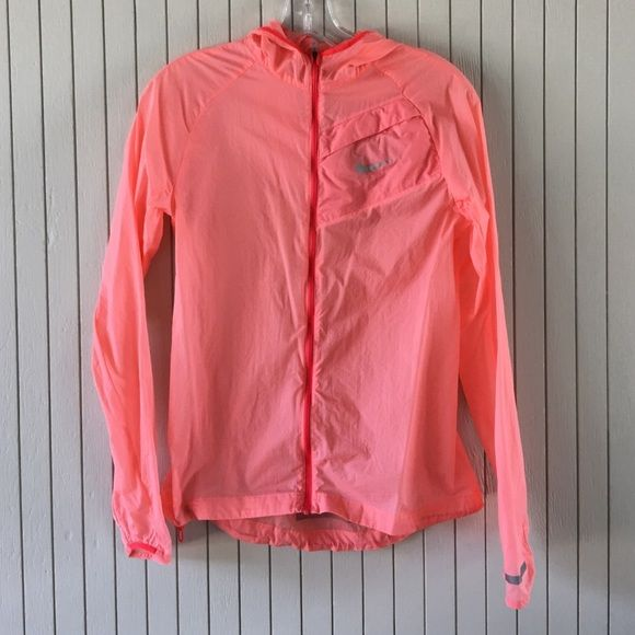 New nike lightweight windbreaker New without tags. It was only used on a photo shoot. Lightweight wind breaker with some reflective marks on the wrists and back. Small zip pocket at left chest and has a hood. It's a light peach/salmon color with darker contrast trim Nike Jackets & Coats Utility Jackets