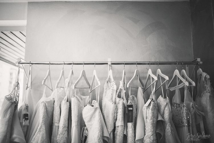 Bride is getting ready while wedding dresses are hanging. Wedding Photography by Jere Satamo.