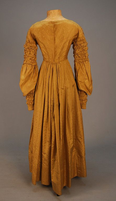 FIGURED SILK GOWN, c. 1840. Olive-gold with vertical dotted stripe alternating with domino and foliate devices, the princess bodice ruched at shoulder and center front point creating fullness at the bust and at top and bottom of long, full sleeve, skirt with gentle pleats at set in waist, self piping, single tuck at hem, bodice and hem band lined in natural linen. B-31, W-22, L-51. (Armpit stains, tiny hole, few spots and scattered discoloration) good. $600-800