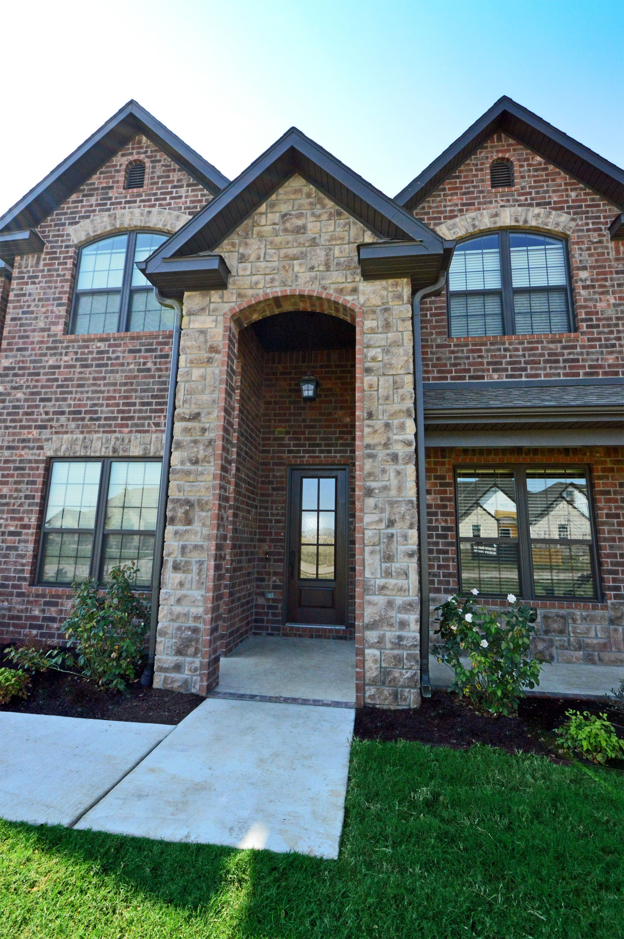 Brick and stone exterior featuring stone archway dark bronze windows and 6 lite 8 39 entry door for Exterior window trim for brick home