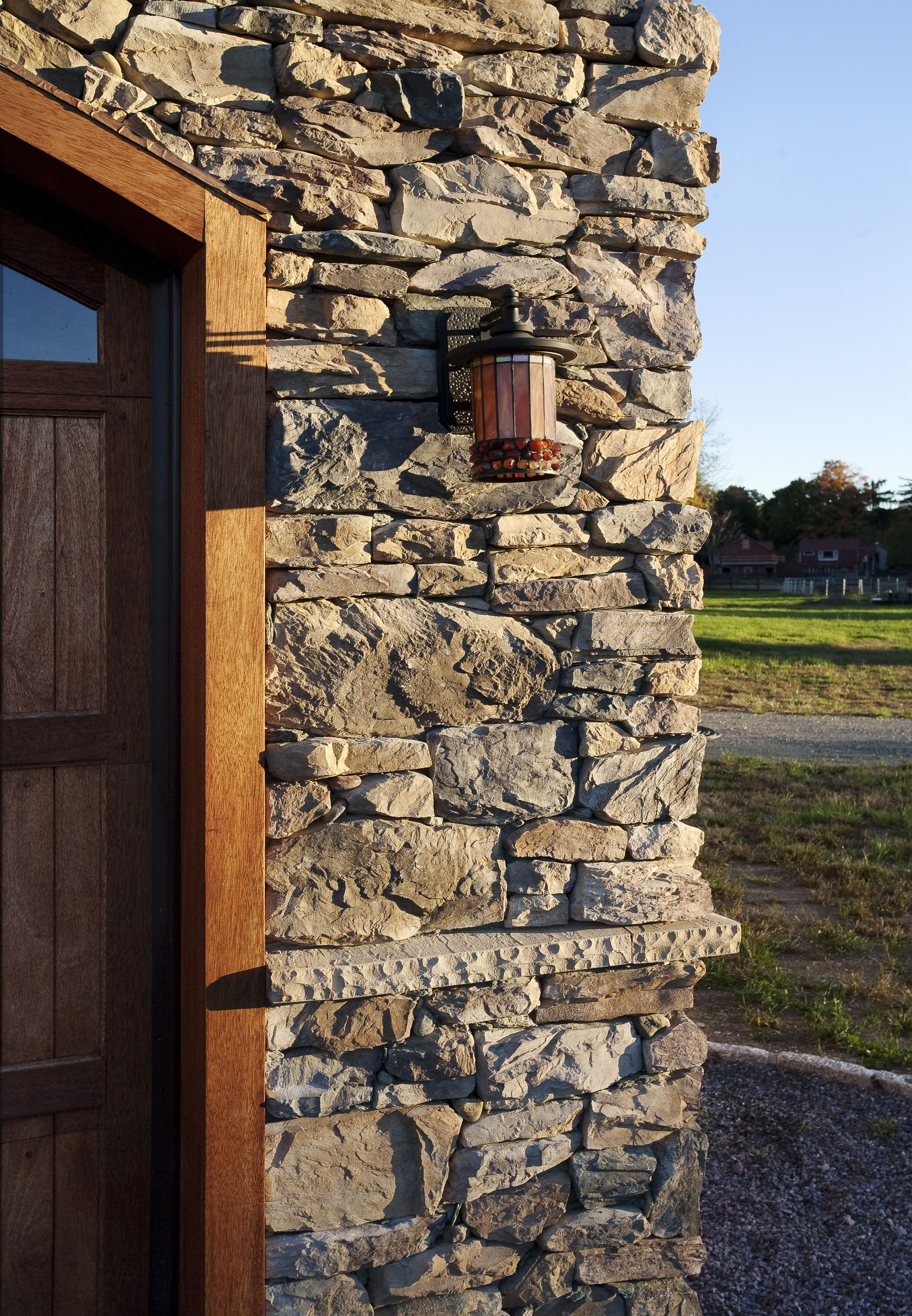 Dry Stack Stone Facade Garage With Wood Garage Doors And Outdoor