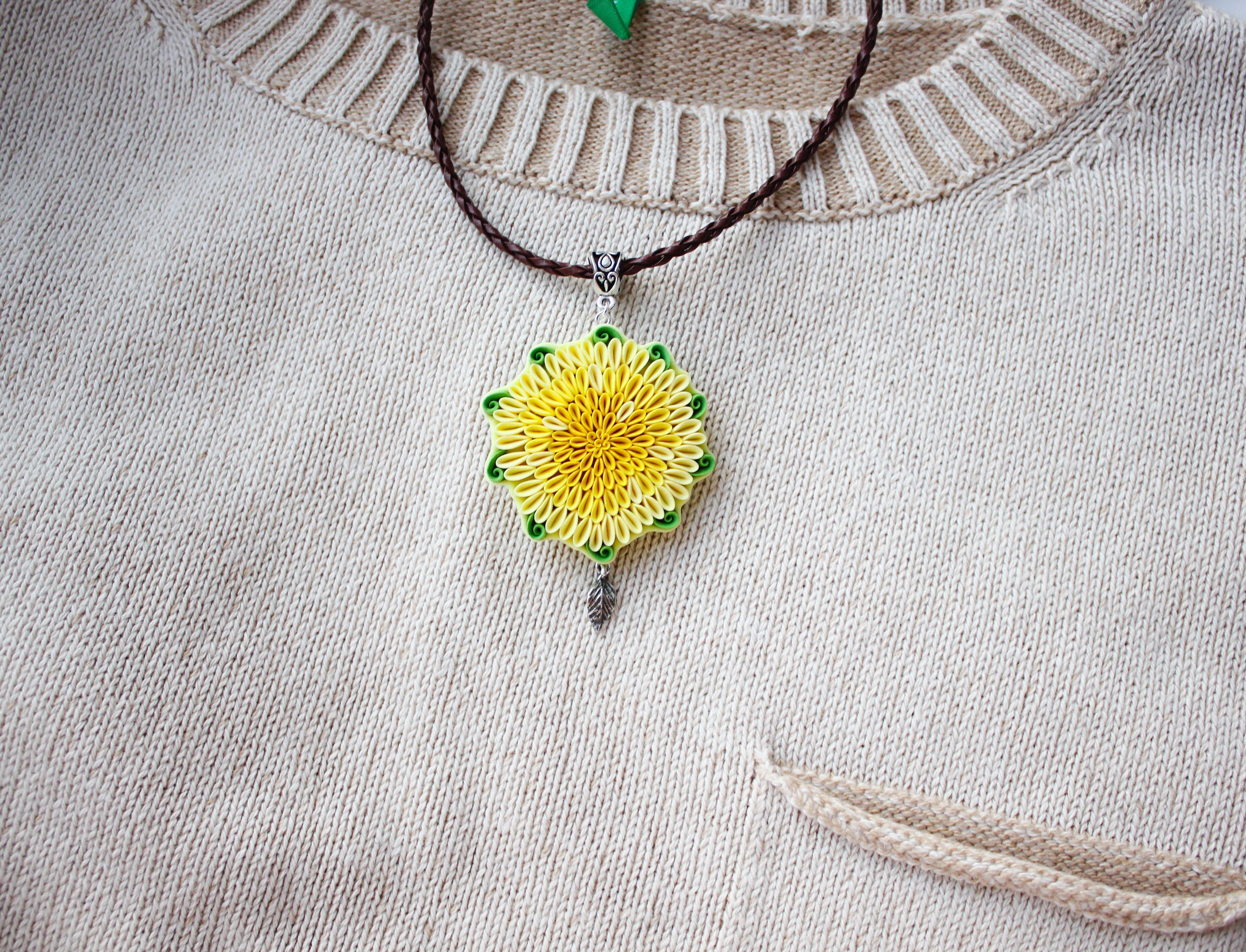 Yellow flower necklace with green leaves in boho style polymer round
