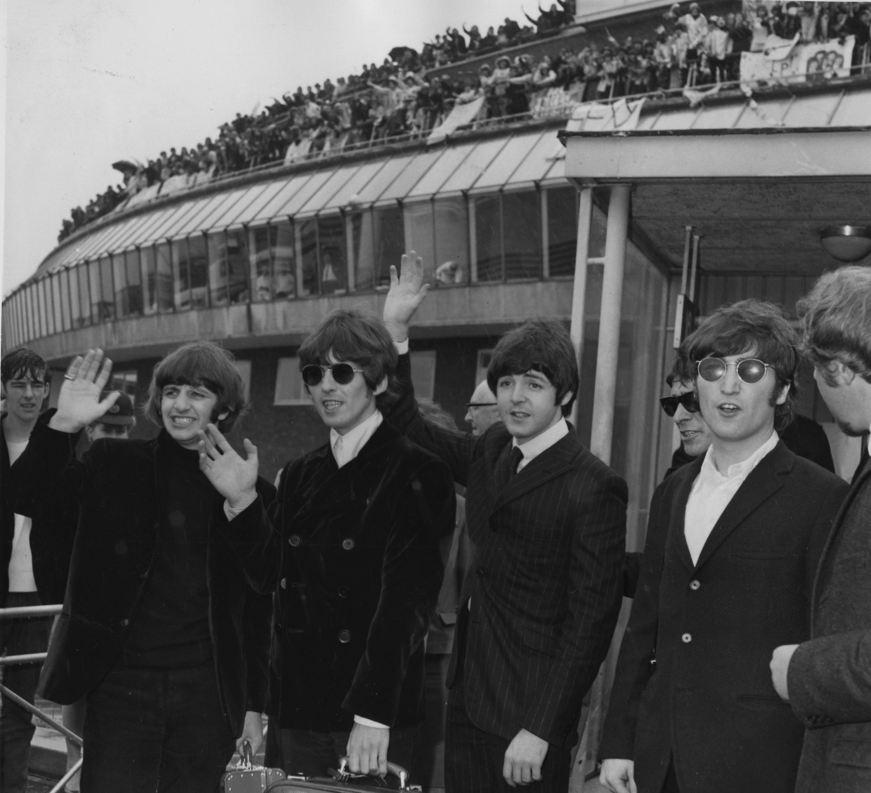 The Beatles, with Ringo Starr, George Harrison, Paul McCartney and John Lennon, from left to right, are pictured in the rain waving at the airport in London, England, August 11, 1966, prior to their departure to Boston, USA, for their tour of Canadian and American cities. (AP Photo/Harris)
