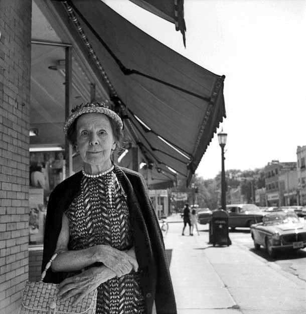 An older woman with pearls, a demure smile, a hat, a purse, and crossed arms looking straight at the camera while on a street in Wilmette. See a Stunning New Set of Vivian Maier Photos from Eye to Eye | Chicago magazine | July 2014