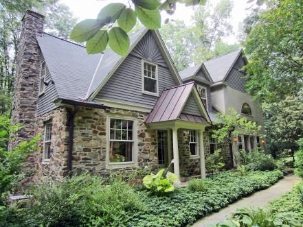 Beautifully updated, this historic Brandywine Valley, Penn. farmhouse features stacked fieldstone, dormer windows and a pitched gable roof. Warm gray paint contrasts beautifully with the stone facade.