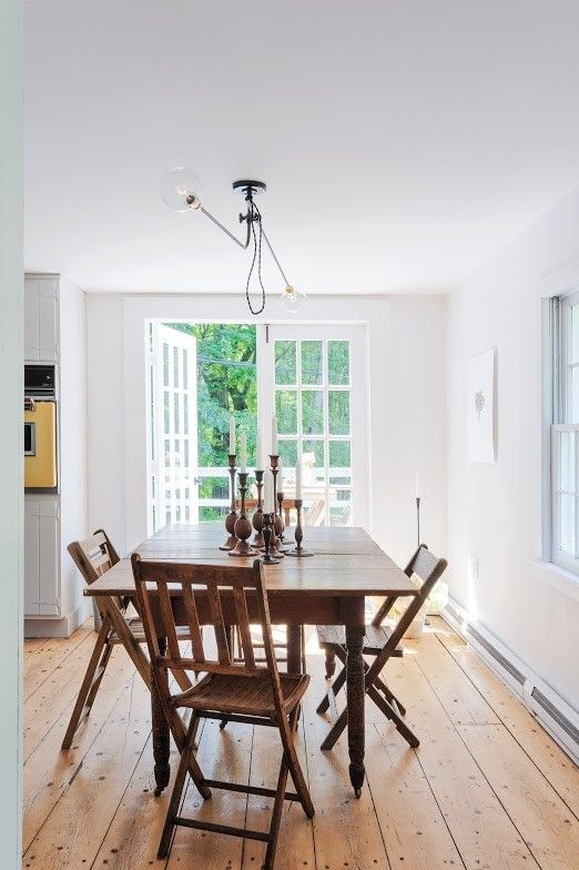 Humble cottage dining area with knotty pine flooring and modern pendant light.