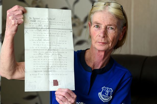 Everton fan Kath McVey holds a contract signed by Johnny Holt in 1889.