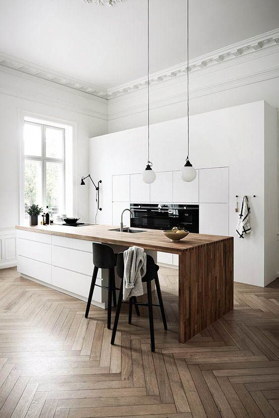 a minimalist Nordic kitchen with sleek white cabinets, a sleek white kitchen island with a wooden waterfall countertop and pendant lamps #whitekitchen #waterfallcountertop