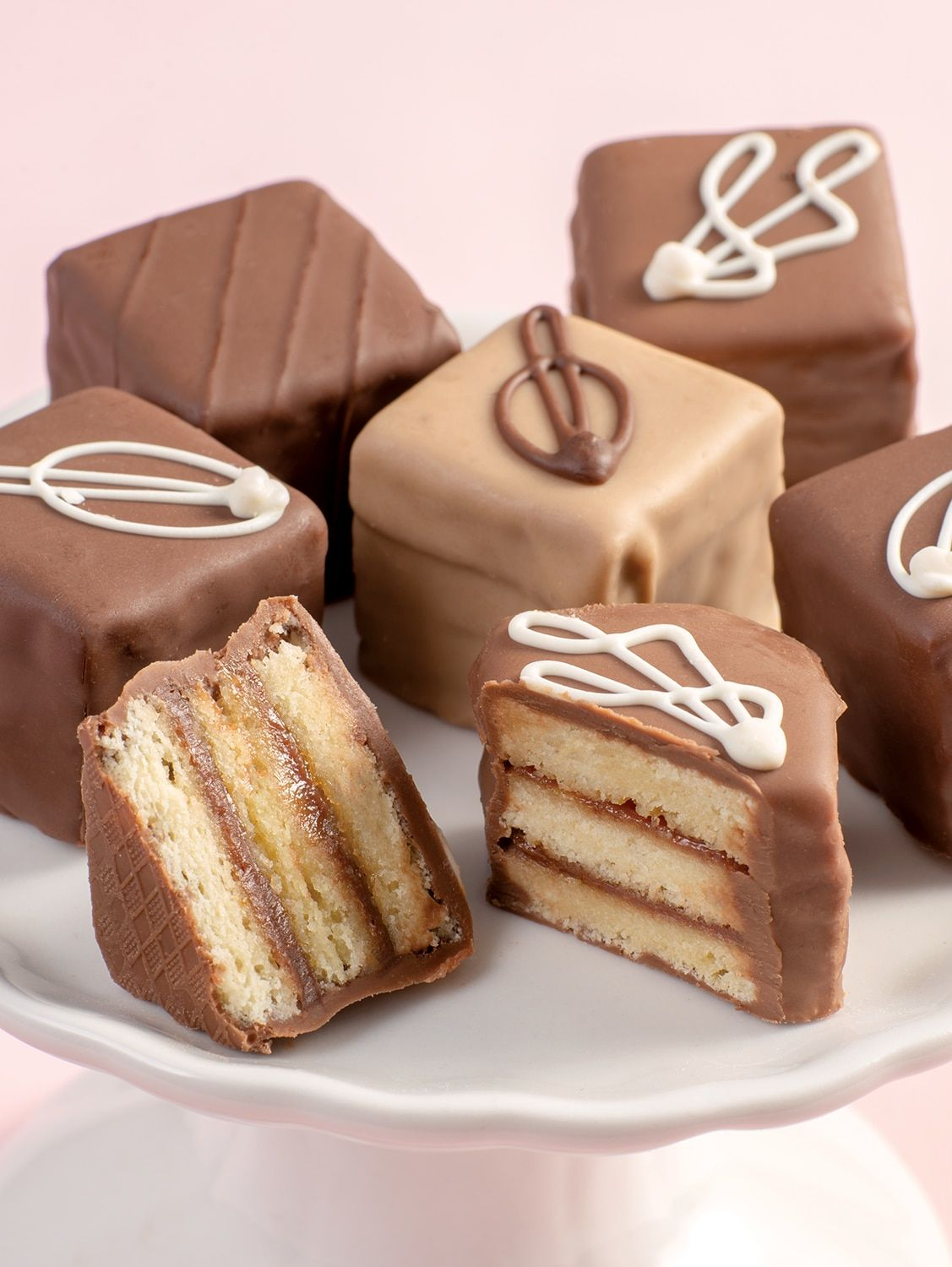 These mini multi-layered cakes are a chocoholic's dream come true! These pretty multi-layered cakes are made using only the finest ingredients to ensure they're always rich, moist, and satisfying. Each box includes 12 petits fours in 4 varieties: butter cake filled with espresso cream, butter cake filled with triple truffle cream, butter cake filled with milk chocolate cream, and butter cake filled with raspberry truffle cream. Each cake is drenched in rich milk or dark chocolate. Rich butter ca