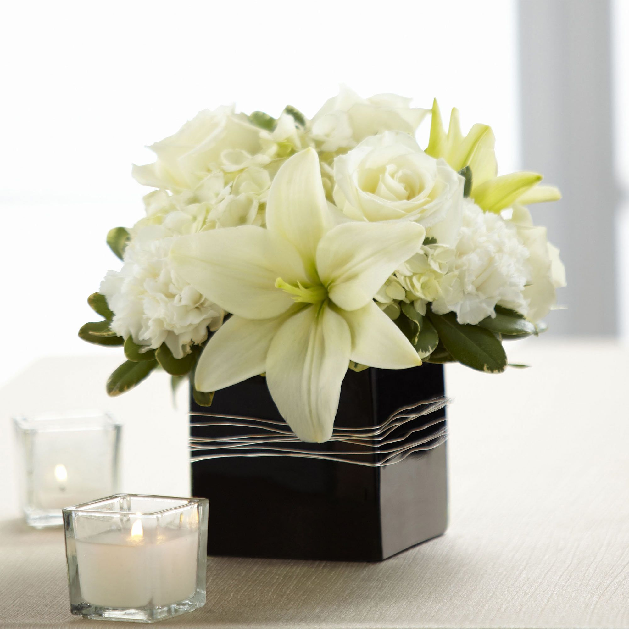 Decorate your home with this lavish arrangement containing white white roses asiatic lilies carnations and hydrangea are offset by lush greens and arranged in a designer black ceramic cube vase reviewsmspy