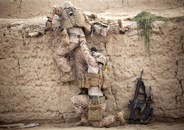 Cpl. Enrique Torres (right), a squad leader with 1st Platoon, Kilo Company, 3rd Battalion, 3rd Marine Regiment, and a 21-year-old native of Alvarado, Texas, helps Lance Cpl. Joseph Hevia, a rifleman and 20-year-old native of Windsor, Calif., climb onto a roof while searching a compound.