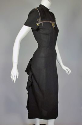 This black rayon crepe cocktail dress from the late 1940s has a high neckline and padded shoulders accented with an ornate appliqué of dark blue sequins and bright yellow glass beads. In back the bodice has a keyhole opening below two hooks at the neck. Below the wide inset waist panel, the skirt is simple and straight in the front, but in the back it has a wonderful ruffle below the hips that drapes down each side of the skirt to the hem. There are two diagonal pleats over the back of each…