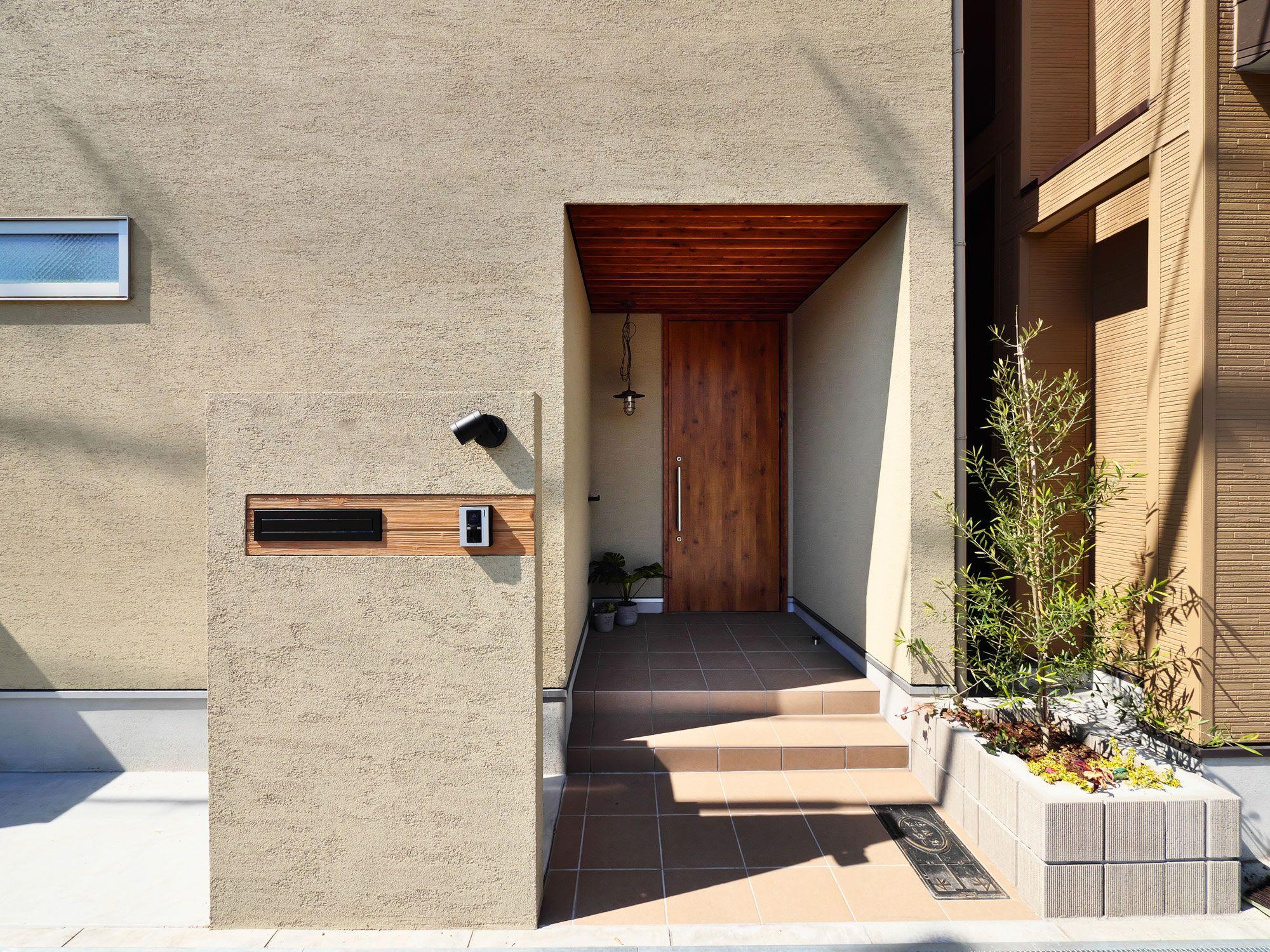 ベージュ色の外壁と木目で統一されたまとまりのある玄関アプローチ