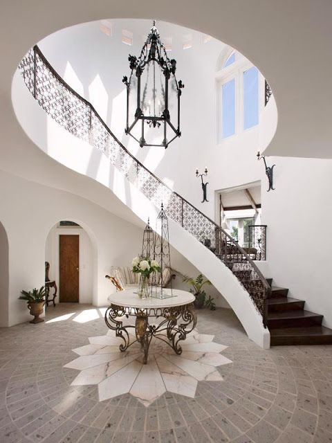 Foyer with two story iron railing stairs, a stone floor with a marble sunburst, a round table with iron work legs and Moroccan inspired ironwork