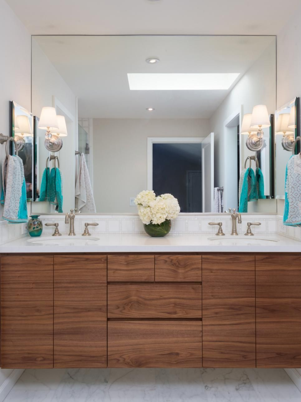 a custom walnut floating vanity by terri robison design helps maximize space in this bathroom