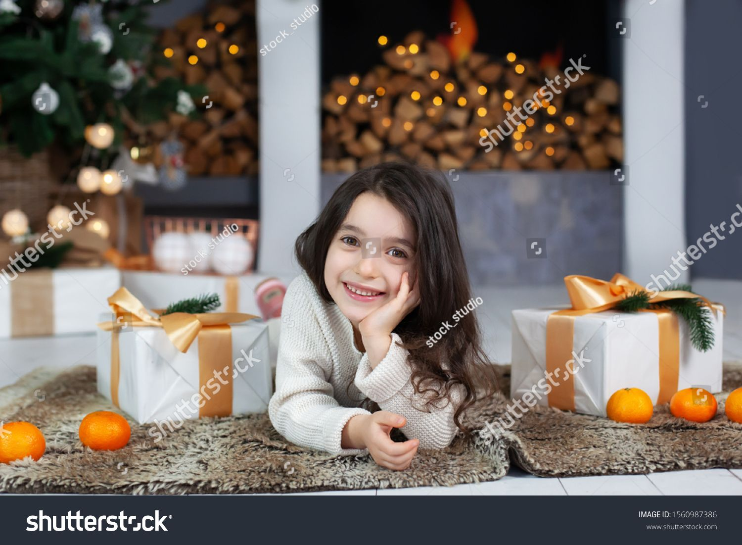 New Year. Smiling girl with gifts near Christmas tree and