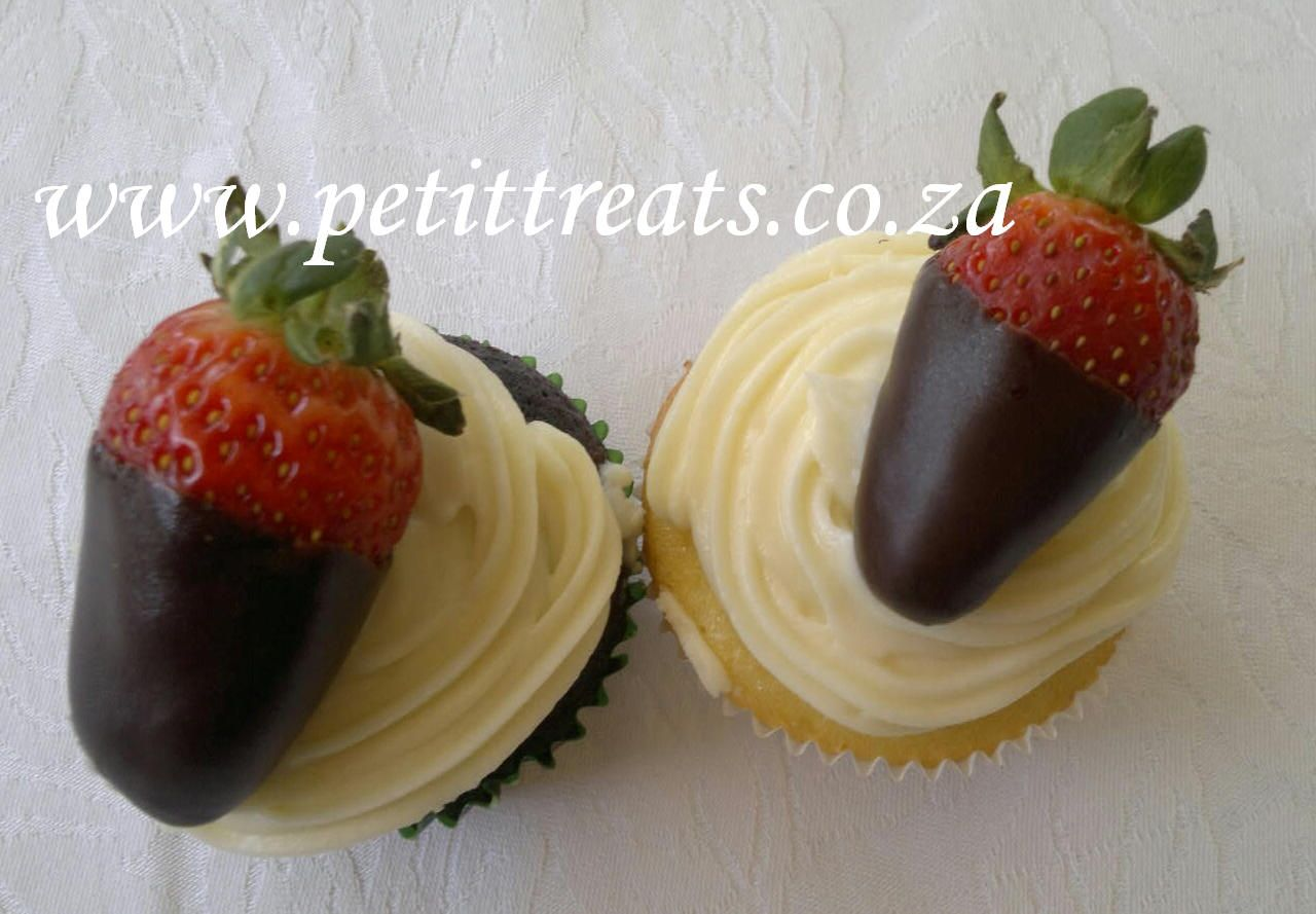Vanilla and chocolate cup cakes topped with cream cheese icing and strawberries dipped in dark chocolate