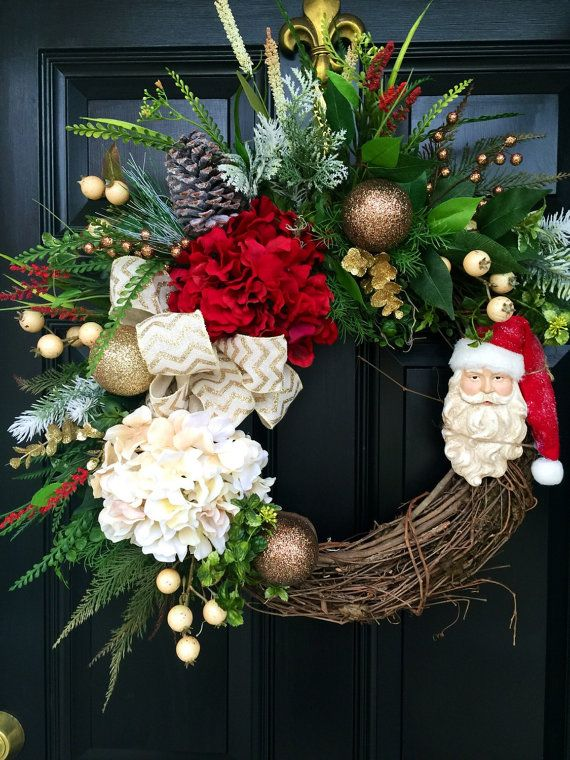 MERRY CHRISTMAS!!  Newest item just added to my store! This wreath is GORGEOUS and so bright and colorful!  Shown on an 18 grapevine base with moss, beautiful mixed flowing greens of ferns, ivies, evergreens, ficus leaves and more. Beautiful hydrangeas of red and cream, cream and gold berries, mixed evergreens, gold sparkly eucalyptus, gold/brown ornaments, accents of red, snow covered pine cones, A gorgeous cream with gold chevron and a decorative gorgeous Santa face ornament make this…