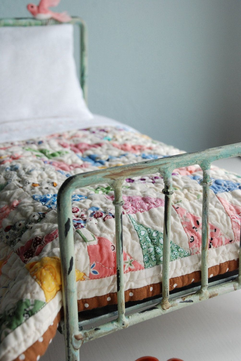 Old bed frame, patchwork quilt, and stuffed bird perched