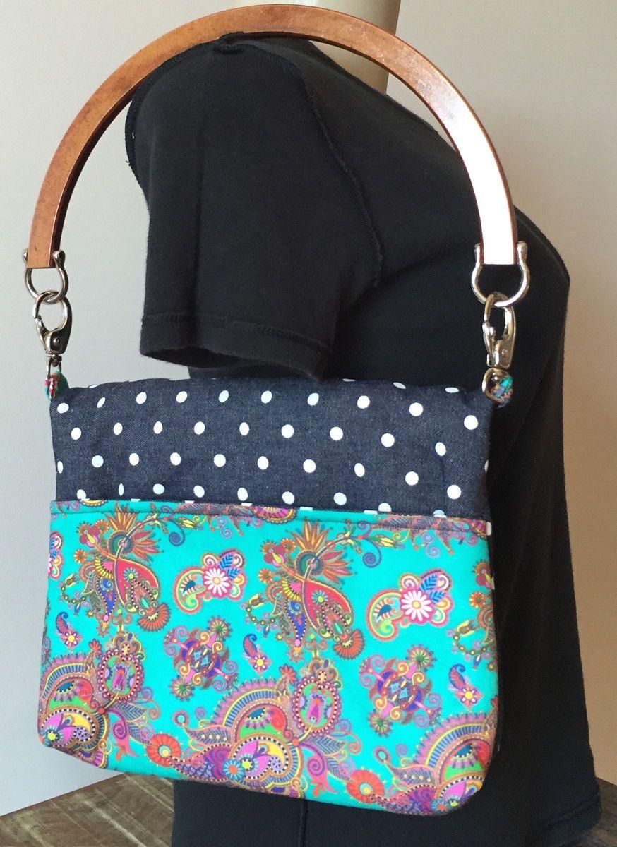 Bolsa em tecido jeans. <br>Com fechamento com dobra e botão. <br>Bolso externo feito com o mesmo tecido do forro.