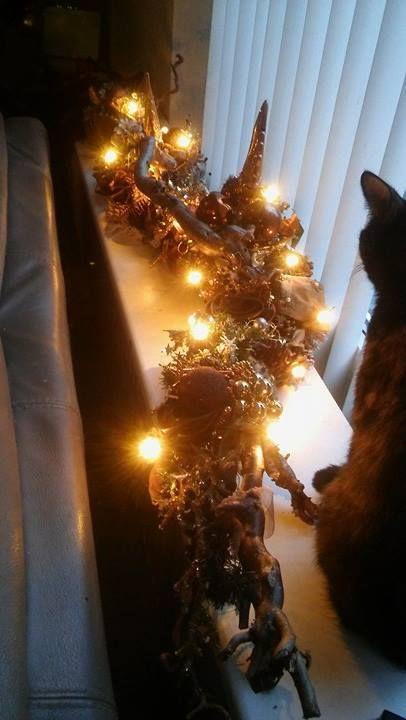 Krulhazelaar tak versierd met kerstlichtjes en kerstversiering. Natuurlijk van de kringloopwinkel e.d.