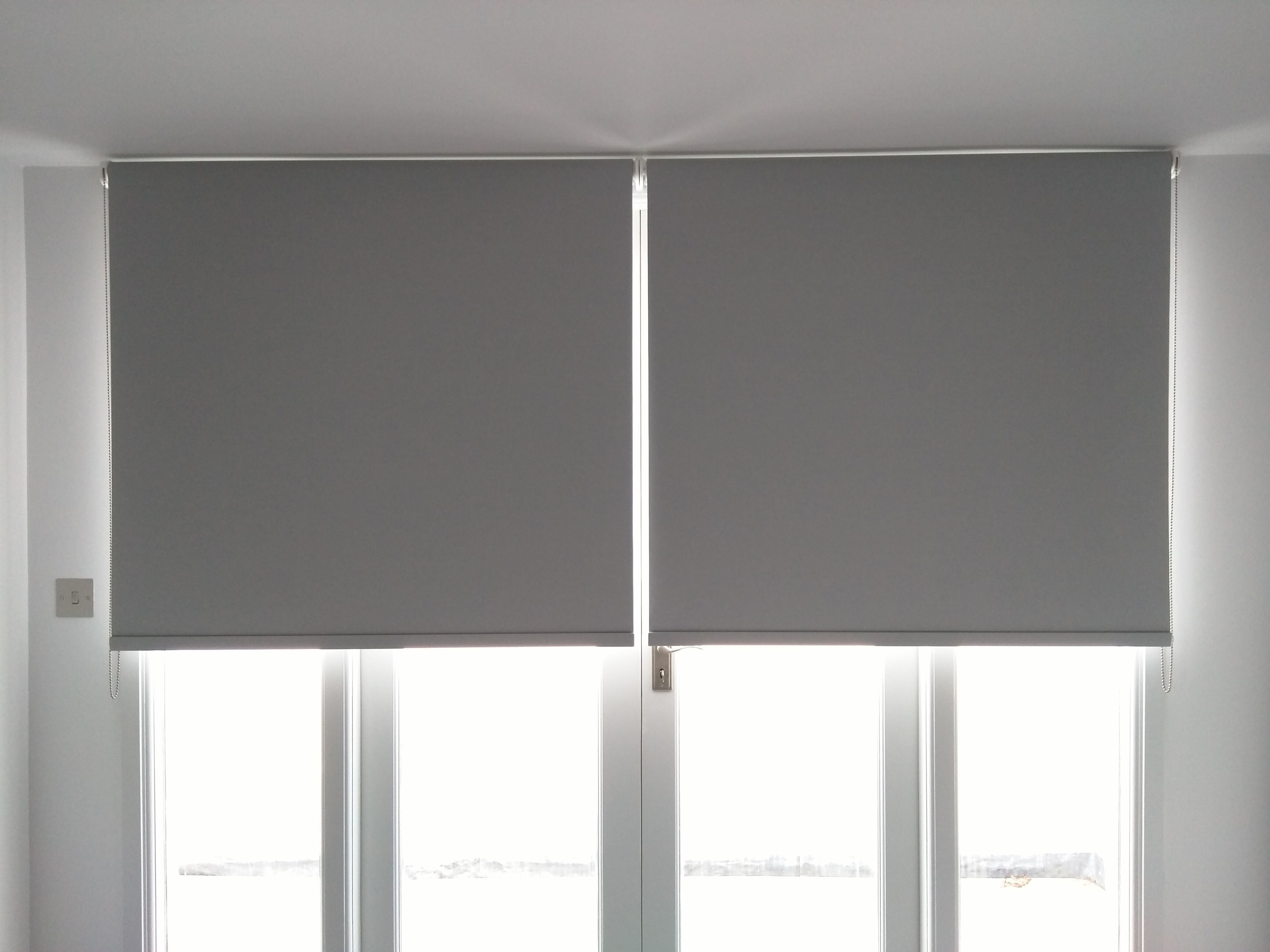 Blackout roller blinds fitted to french doors in new apartment