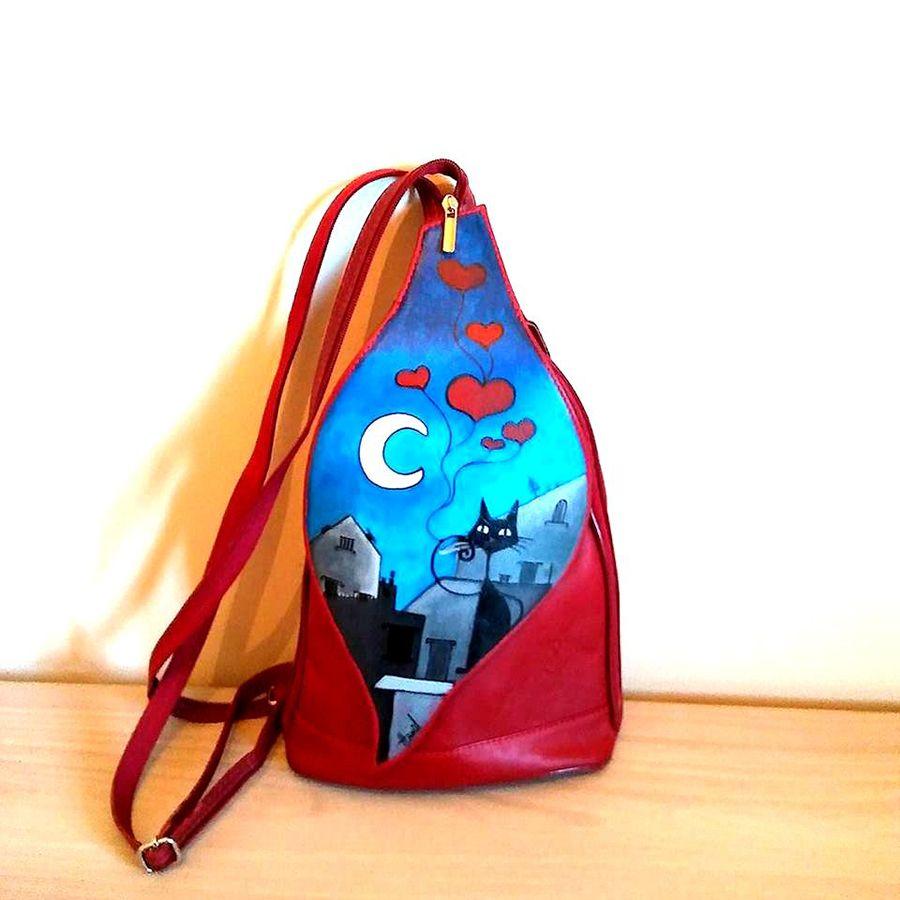 Borsa Zaino in pelle dipinto a mano, color rosso, con dipinta a mano una scenetta simpatica di un paesaggio stilizzato con un gatto nero in primo piano. Colori duraturi, irreversibili e luminosi.