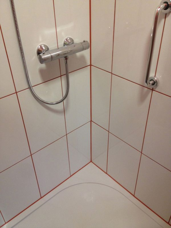 Bathroom Grout white tiles with red silicone and grout with bathroom installation