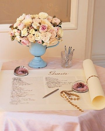 Paperweights decoupaged with roses anchor a parchment-color paper scroll for family and friends to sign, and a vintage ribbon fastens it closed. Above it, snowberries and garden roses are arranged in an antique blue-enamel loving cup.