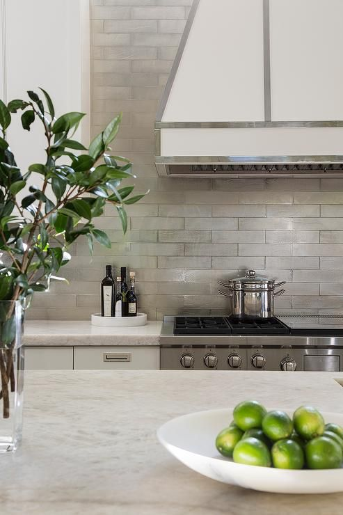 White And Ivory Kitchen Boasts An Ivory Range Hood Accented With Stainless  Steel Trim Over A