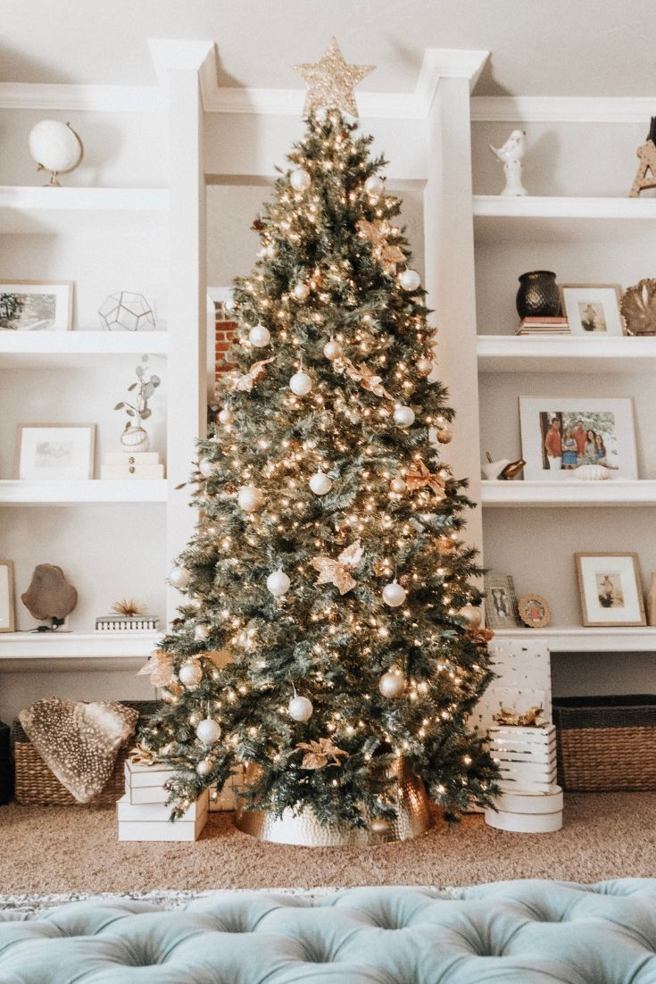 Christmas Decorations, green Christmas tree, white lights, gold bows, white and gold ornaments, white and gold wrapping paper and white gift boxes in front of built-in shelves styled with curated items. Modern Glam Christmas ideas, Christmas decorating ideas.