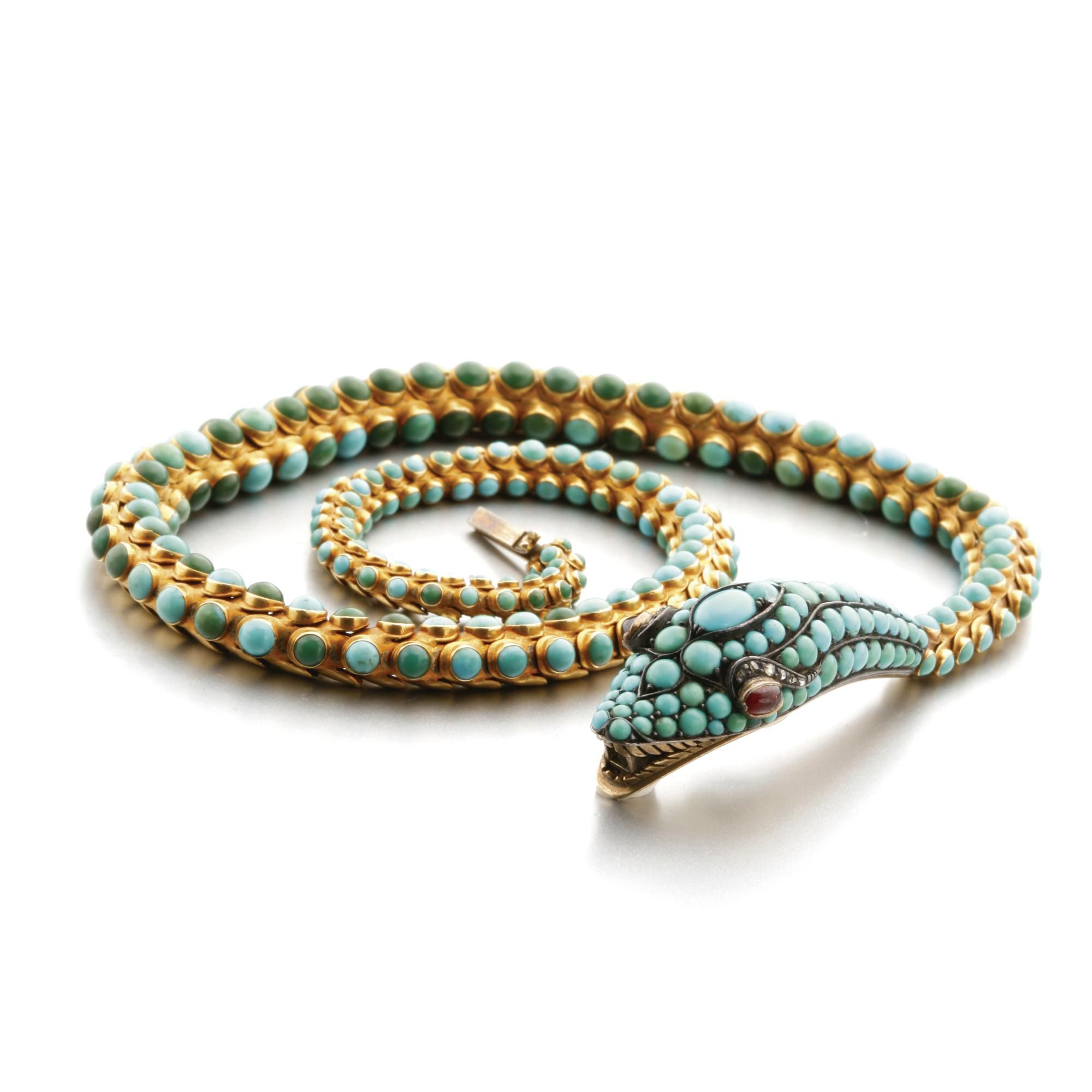 GOLD, SILVER AND TURQUOISE SNAKE NECKLACE, MID 19TH CENTURY The serpent with flexible, tapering body, studded with turquoise cabochons, the eyes set with oval red stone cabochons beneath scrolls of rose-cut diamonds, a glazed compartment under chin, mounted in gold and silver.