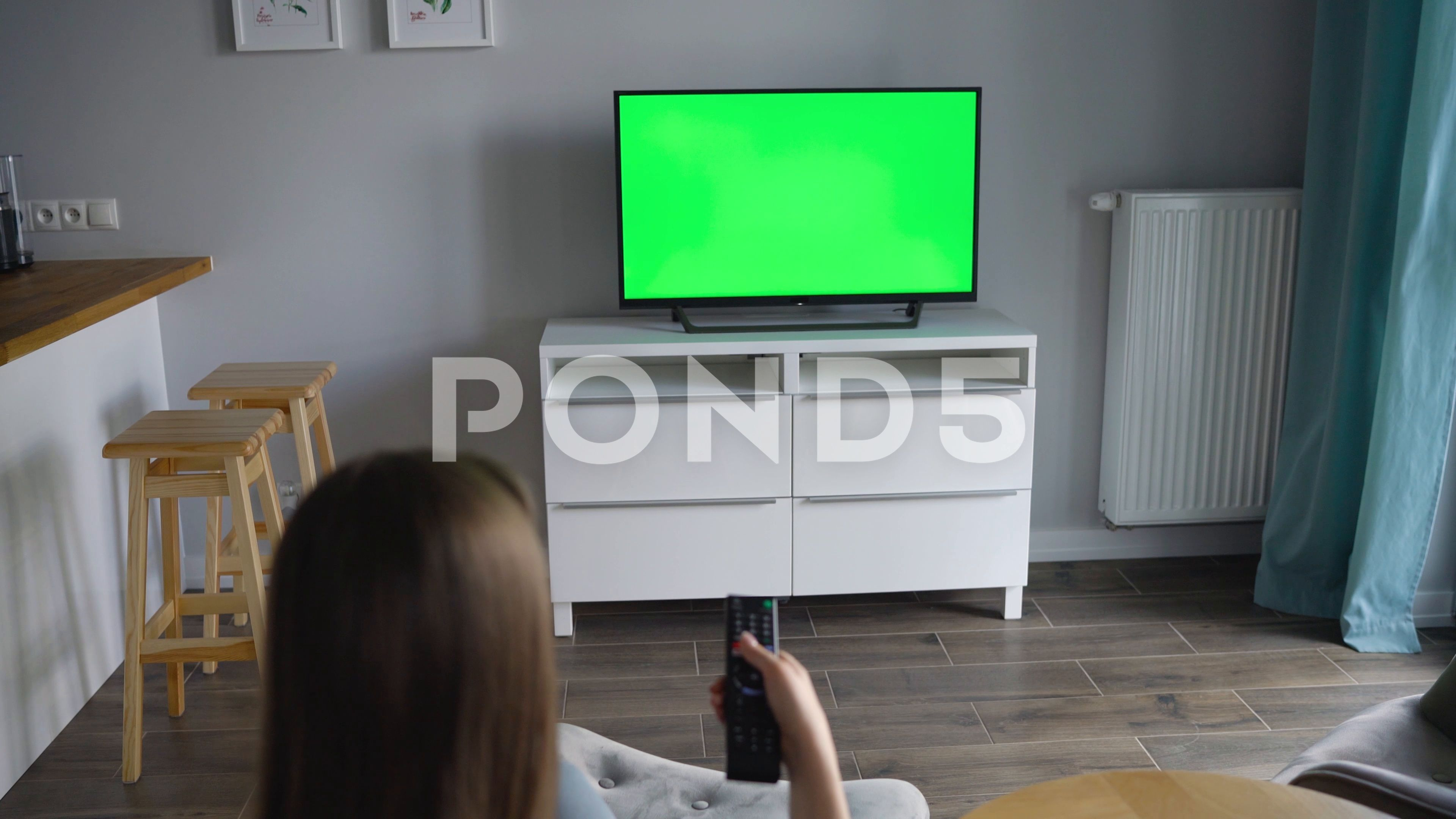 Woman Is Sitting In A Chair Watching Tv With A Green Screen Switching Channels Stock Footage Ad Watching Tv Chair Woman Greenscreen Chroma Key Stock Video