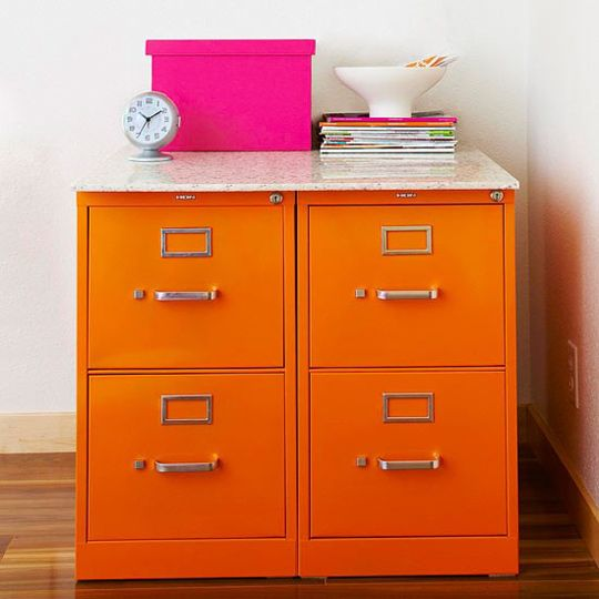 Paint your filing cabinets an eye-popping color and top with a scrap piece of stone, granite or concrete from a local homebuilding shop. All the sudden filing looks like a pleasing activity… sort of.  (via Apartment Therapy from BH+G)  Original Article
