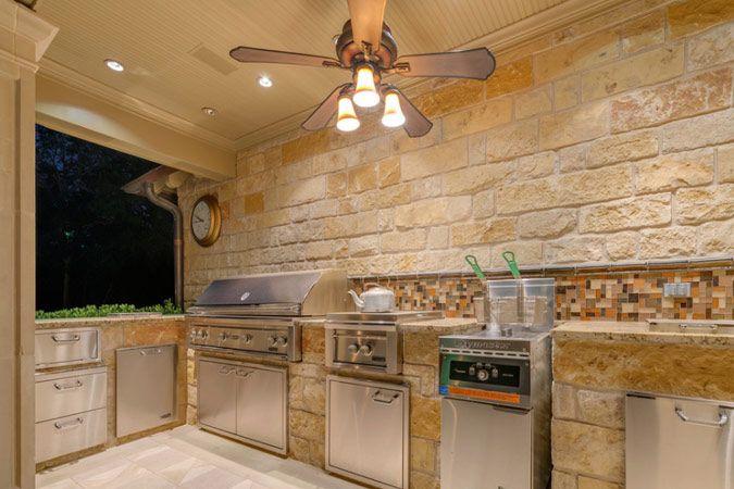 Buitenkeuken in natuursteen met inox kastjes a
