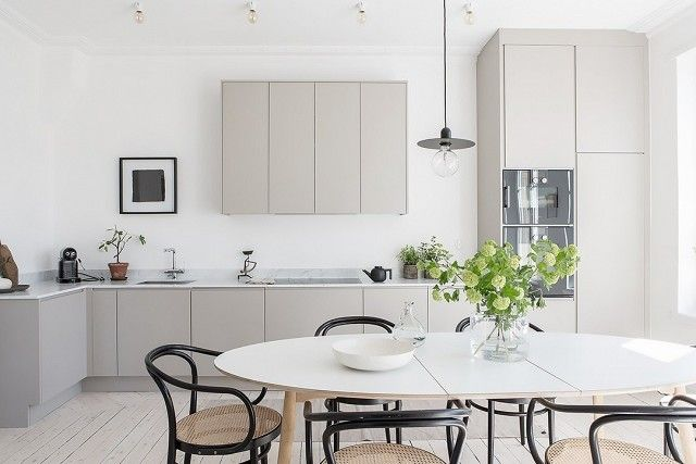 A minimalist kitchen with gray cabinents, and a simple pendant light over a dining table